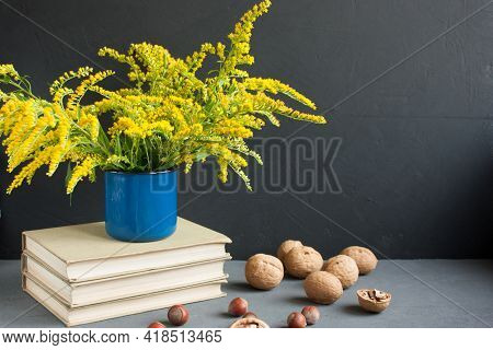 Bouquet Of Delicate Yellow Flowers Of Canadian Goldenrod In A Blue Enameled Mug On A Stack Of Books.