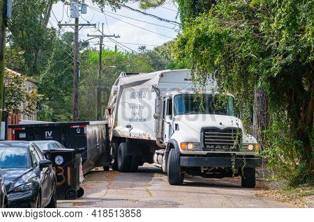 New Orleans, La  - October 21: Sanitation Truck Stuck Between A Dumpster And A Parked Car In An Upto