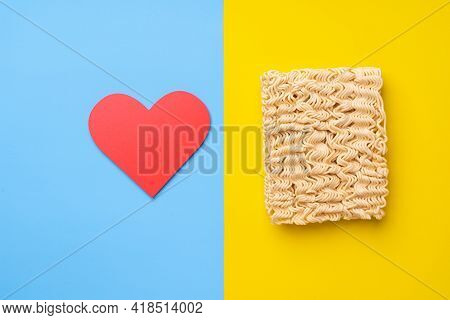 Dry Instant Noodles And Red Heart On Yellow And Blue Background. Top View