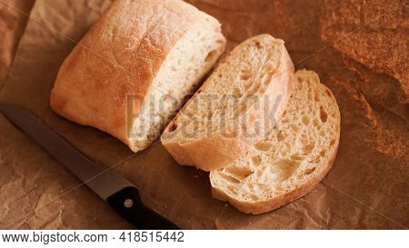 The Chef Slices The Ciabatta With A Knife. Ciabatta Slices On Craft Paper