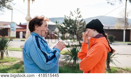 Grandmother Scolds The Adult Granddaughter, Standing On The Street. Negative Communication And Probl