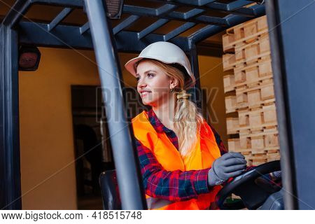 Smiling Woman Driving Forklift Truck At The Warehouse