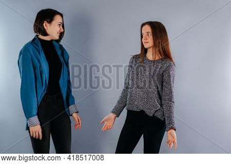 Two Happy Girls Are Looking At Each Other In Surprise