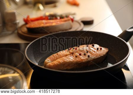 Frying Pan With Tasty Salmon Steak On Cooktop