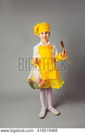 The Little Girl Is Posing In A Chefs Costume