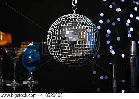 Shiny Disco Ball Hanging Over Bar Counter With Cocktails In Nightclub