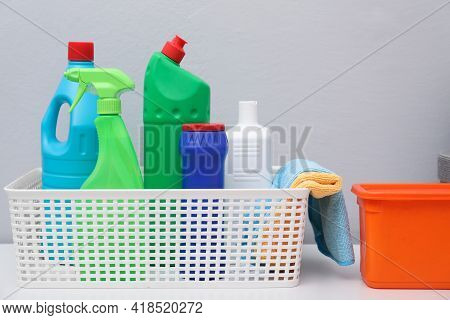 Basket With Detergents And Rags On White Table Against Light Grey Background