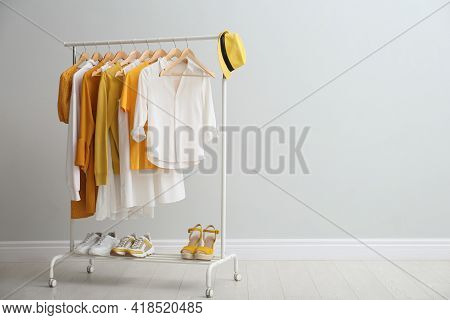 Rack With Bright Stylish Clothes, Hat And Shoes Near Light Grey Wall Indoors, Space For Text