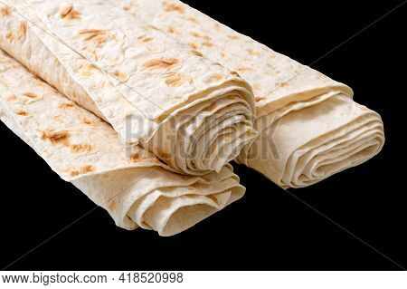 Rolled Up Thin Pita Bread Isolated On Black Background. Lavash - Tasty Hearty Healthy Armenian And T