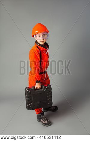 The Little Girl In An Engineers Uniform With Goggles And Box