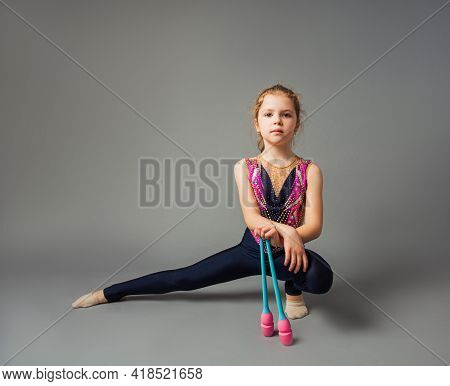 The Little Girl Gymnast Is Posing With Instruments
