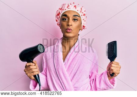 Hispanic man wearing make up wearing shower cap holding hair dryer and comb looking at the camera blowing a kiss being lovely and sexy. love expression.