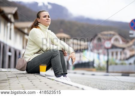The Female Sits On The Side Of The Road, On The Sidewalk. Desperate Woman Lost In The City. Girl Cry