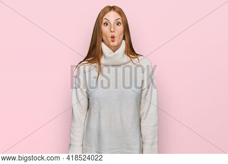 Young irish woman wearing casual winter sweater making fish face with lips, crazy and comical gesture. funny expression.