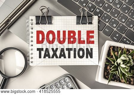 Double Taxation Text On A Notepad And Laptop, Office Tools. Business, Financial Concept. Remote Trai
