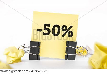 Minus 50 Percent On A Yellow Piece Of Paper For Notes. Stationery Paper Clips, Crumpled Paper. Finan