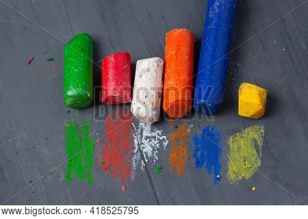 Battered Small Wax Crayons On A Gray Textured Background With Multicolored Strokes