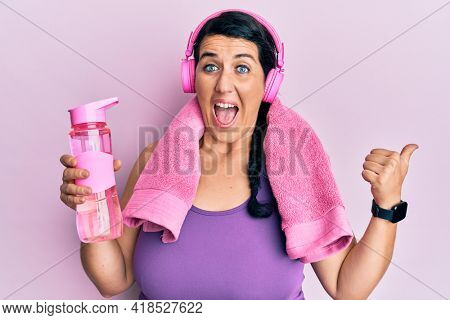 Plus size brunette woman wearing sportswear holding water bottle pointing thumb up to the side smiling happy with open mouth
