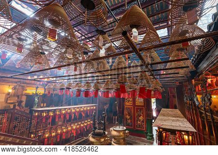 Sheung Wan, Hong Kong: July. 07, 2019 - Incense Coils And Interior Of Man Mo Temple, One Of The Famo