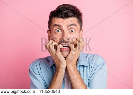 Photo Of Scared Shocked Young Man Bite Nails Hold Hands Mouth Isolated On Pastel Pink Color Backgrou