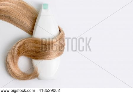 Shampoo Or Conditioner Bottle Wrapped In Lock Of Curly Blonde Hair Isolated On Light Background, Top