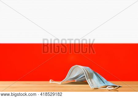 A Medical Mask Lies On The Table Against The Background Of The Flag Of Poland. The Concept Of A Mand