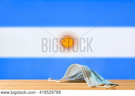 A Medical Mask Lies On The Table Against The Background Of The Flag Of Argentina. The Concept Of A M