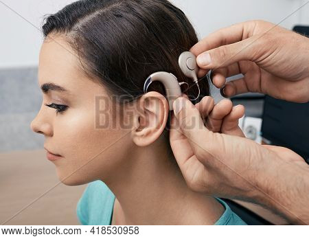 Cochlear Implant. Installation Cochlear Implant On Womans Ear For Restores Hearing