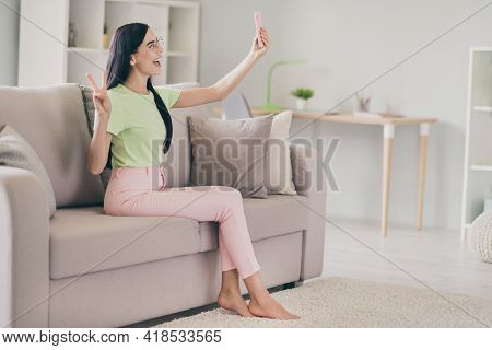 Photo Of Lovely Girl Sit Sofa Hold Phone Make Selfie Show V-sign Open Mouth Barefoot Wear Specs Gree