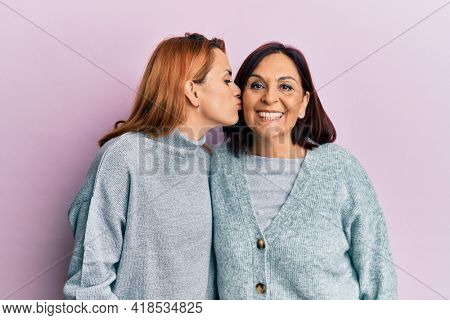 Latin mother and daughter wearing casual clothes looking at the camera blowing a kiss on air being lovely and sexy. love expression.