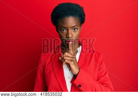 Young african american girl wearing business clothes asking to be quiet with finger on lips. silence and secret concept.