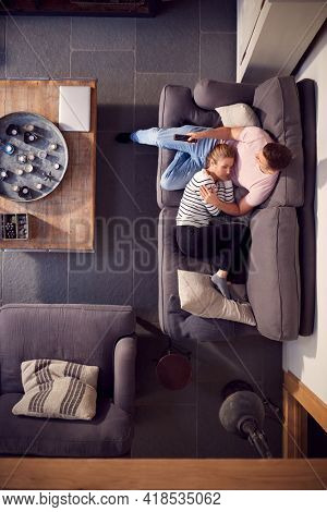 Overhead View Of Couple Relaxing On Lounge Sofa Having Afternoon Nap At Home And Watching TV