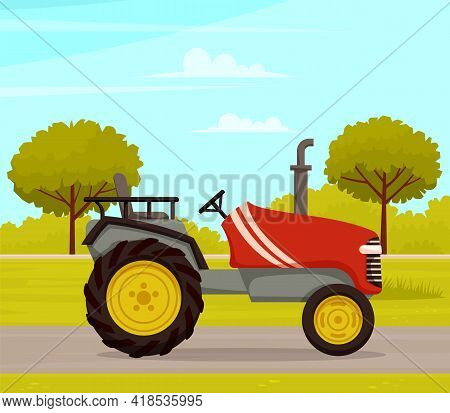 Driving Tractor On Road Near Meadow On Nature Landscape. Driving Red Tractor, Agrimotor Cabin. Agric