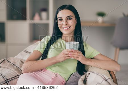Close-up Portrait Of Charming Cheery Calm Long-haired Girl Sitting On Cosy Checkered Cover Drinking