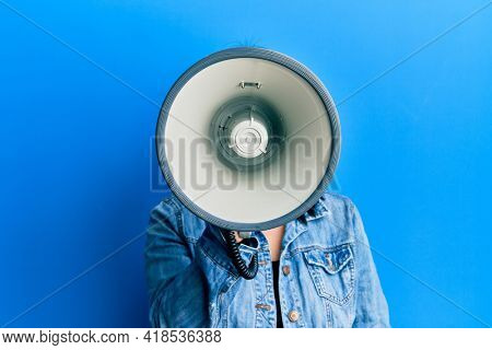 Young plus size woman shouting using megaphone