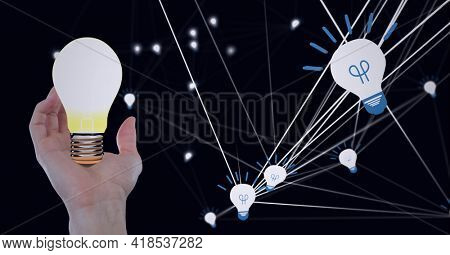 Composition of lit light bulb over hand with network of light bulb icons on black background. lightbulb moment, electricity, inventions and technology concept digitally generated image.