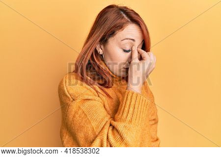 Beautiful redhead woman wearing casual winter sweater over yellow background tired rubbing nose and eyes feeling fatigue and headache. stress and frustration concept.