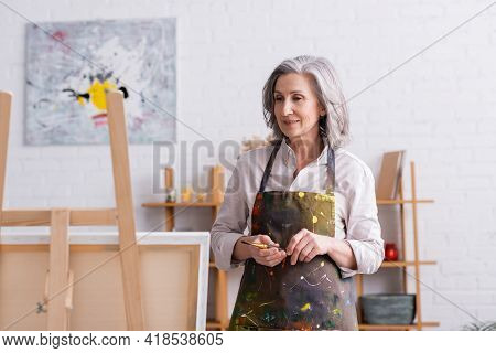 Pleased Middle Aged Artist In Apron With Spills Holding Paintbrush And Looking At Canvas On Easel.