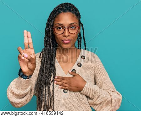 African american woman wearing casual clothes smiling swearing with hand on chest and fingers up, making a loyalty promise oath