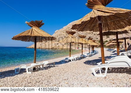 View Of The Straw Umbrellas In The Beautiful Oprna Beach In The Adriatic Bay Of The Krk Island, Croa
