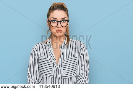 Young caucasian woman wearing business shirt and glasses depressed and worry for distress, crying angry and afraid. sad expression.