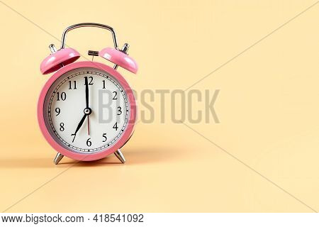 Pink Alarm Clock On A Beige Background. Time Concept. Place For Your Text. Copy Space.