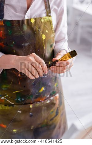 Cropped View Of Middle Aged Artist In Apron With Spills Holding Paintbrush.