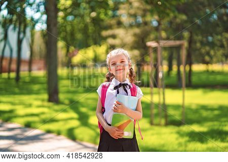 Smiling Student Girl Wearing School Backpack And Holding Exercis