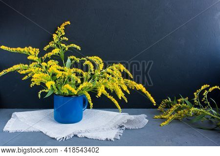 Bouquet Of Canadian Goldenrod In A Blue Enameled Mug On A Linen Napkin On A Gray Background, Twigs W