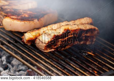 Grilling Steaks On Flaming Grill. Shot With Selective Focus.
