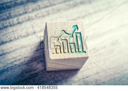 Financial Business Chart With Rising Arrow On A Wooden Block On A Table