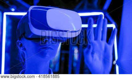 Woman Using Virtual Reality Headset, Moving Hand At Interactive Technology Exhibition With Blue Proj