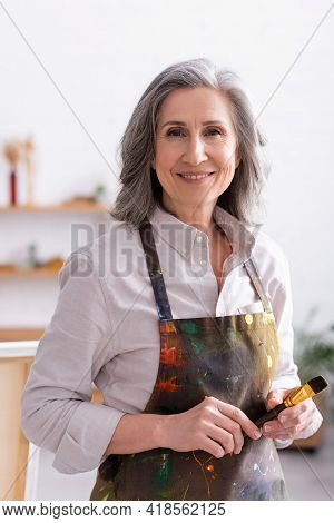 Cheerful Middle Aged Artist In Apron With Spills Holding Paintbrush.