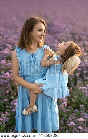 A Mother Holds Her Daughter Tightly In Her Arms In A Blooming Field. Unity With Nature. Mother's Day